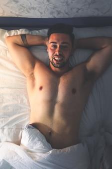 Jonge sexy blanke man naakt op het bed vanuit een zenitale hoek