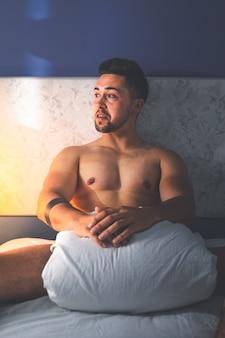 Jonge sexy blanke man naakt op het bed.