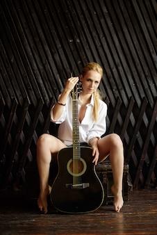 Jonge sexy blonde meisje gitaarspelen