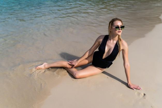 Jonge sexy blonde vrouw die op tropisch toevluchtstrand legt in elegante zwarte swimwear