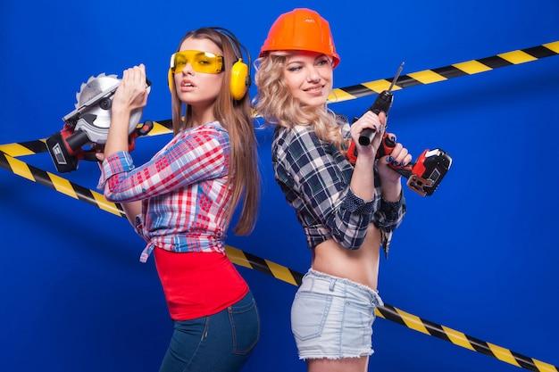 Jonge sexy bouwmeisjes in geruite overhemden, één meisje met boor, tweede met cirkelzaag