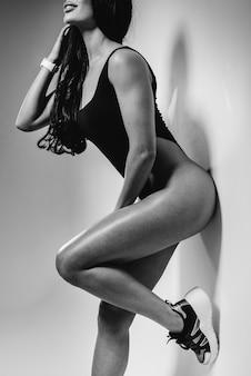 Jonge sexy brunette in een zwarte romper op een witte achtergrond. het perfecte atletische figuur. zwart en wit.