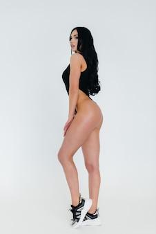 Jonge sexy brunette in een zwarte romper op een witte achtergrond. het perfecte atletische figuur.