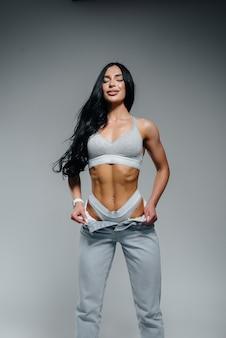 Jonge sexy brunette poseren in lingerie en jeans op een grijze achtergrond. het perfecte atletische figuur.