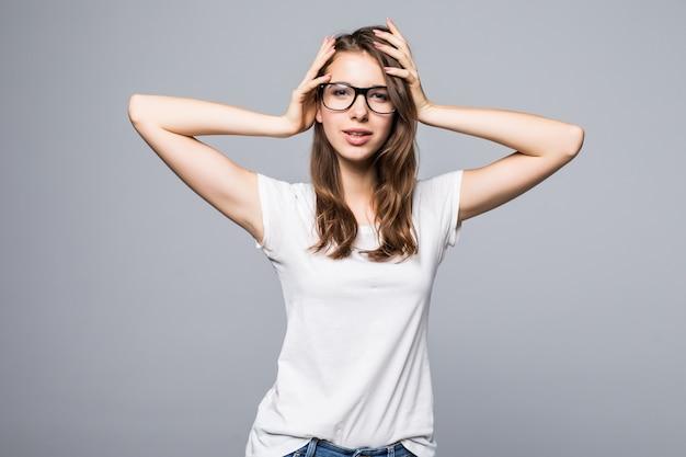 Jonge sexy dame in glazen in wit t-shirt en spijkerbroek houdt haar armen op haar voor witte studio achtergrond