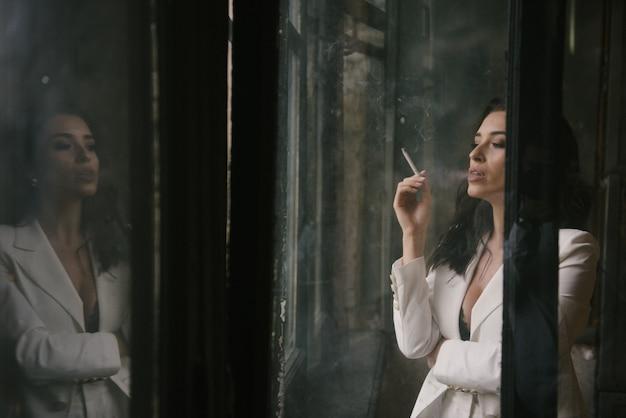 Jonge sexy donkerbruine vrouw in kostuum die een sigaret roken door het venster binnen