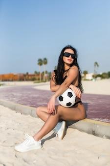 Jonge sexy fit vrouw in zonnebril met voetbal op het strand
