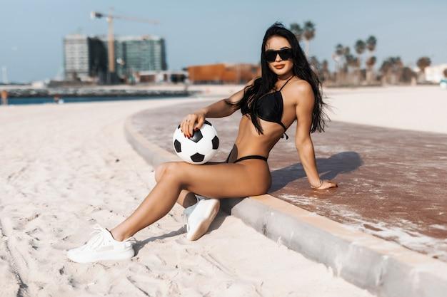 Jonge sexy fit vrouw met voetbal bal zittend op het strand