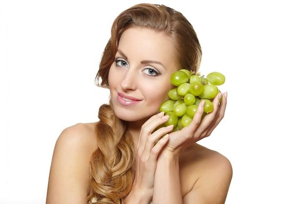 Jonge sexy glimlachende mooie vrouw die een bos van druif in haar handen met lang haar houdt dat op wit wordt geïsoleerd