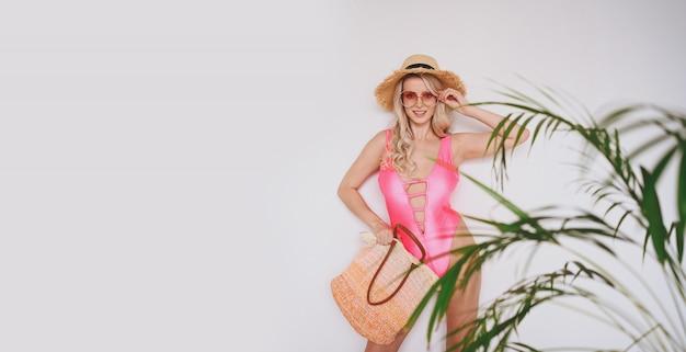 Jonge sexy lachende gelukkig blonde in een roze zwembroek, een strooien hoed, zonnebril, opgewonden om product te presenteren. vrouw op een witte achtergrond met palm groene bladeren.
