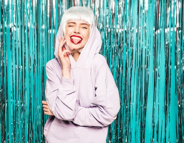 Jonge sexy lachende hipster meisje in witte pruik en rode lippen. mooie trendy vrouw in zomer kleding. toont tong