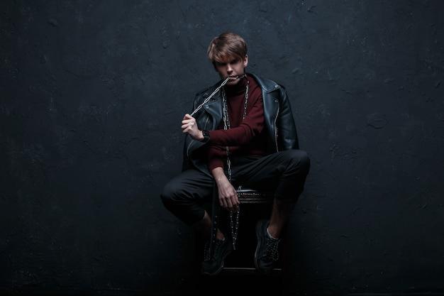 Jonge sexy man met een kapsel in een vintage jasje in bordeauxrode golf in jeans en sneakers zit op een stoel en houdt in zijn tanden een metalen ketting in een donkere studio in de buurt van de muur. de moderne man. mode