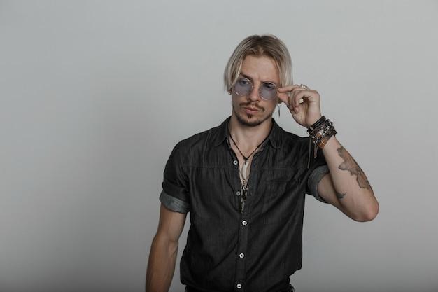 Jonge sexy man met een tatoeage met een stijlvol kapsel met leren armbanden in een modieus zwart shirt