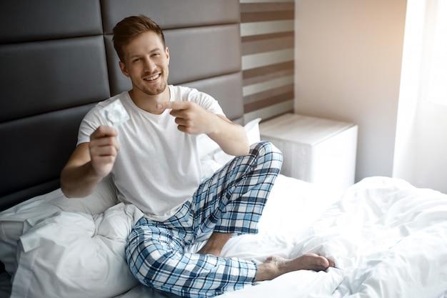 Jonge sexy man op bed vroege ochtend. hij houdt condoom in de hand en wijst erop. glimlachen.