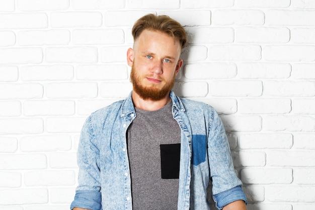 Jonge sexy man tegen een witte bakstenen muur