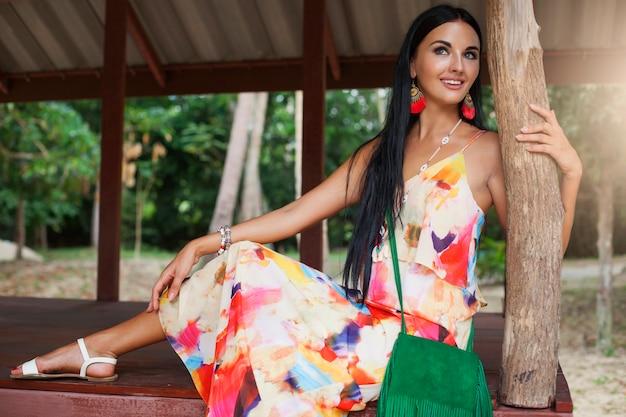 Jonge sexy mooie vrouw in kleurrijke jurk zomer hippie stijl, tropische vakantie, gebruinde benen, sandalen, groene handtas met franje, accessoires, glimlachen, gelukkig