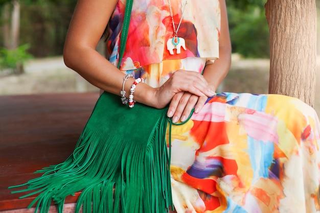 Jonge sexy mooie vrouw in kleurrijke jurk zomer hippie stijl, tropische vakantie, groene handtas met franje, accessoires, handen close-up met armbanden, vingers, manicure