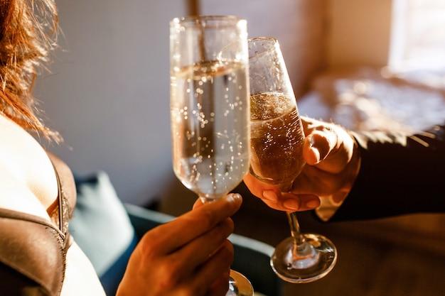 Jonge sexy paar in de woonkamer. sluit omhoog en snijd mening van man en vrouwen de glazen van het holdingsslepen met mousserende wijn. sexy model draagt zwarte beha.