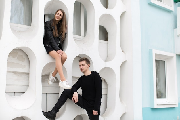 Jonge sexy paar in zwarte kleding poseren met een achtergrond op de witte muur