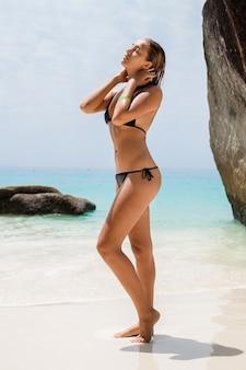 Jonge sexy slanke vrouw, mooi perfect lichaam, gebruinde huid, zwarte bikini badpak, zonnebaden in helderblauwe water oceaan, zomervakantie in azië, sensueel, warm, reizen in thailand, tropisch strand