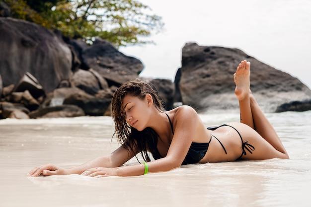 Jonge sexy slanke vrouw, mooi perfect lichaam, gebruinde huid, zwarte bikini badpak, zonnebaden, oceaan, zomervakantie in azië, sensueel, heet, reizen in thailand, tropisch strand, similan-eilanden