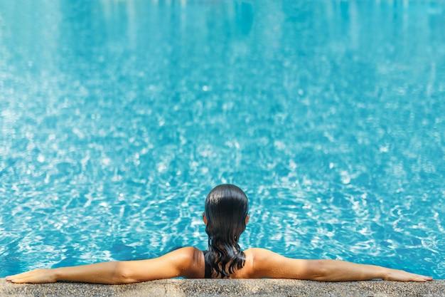 Jonge sexy slanke vrouw ontspannen in tropisch zwembad met kristalhelder water in hete zomerdag
