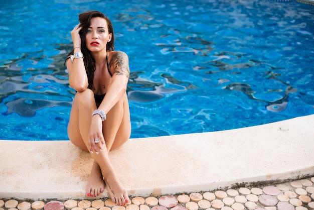Jonge sexy vrouw dicht bij zwembad dat zwart zwemmend kostuum draagt