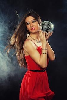 Jonge sexy vrouw die in rode dres discobal houdt