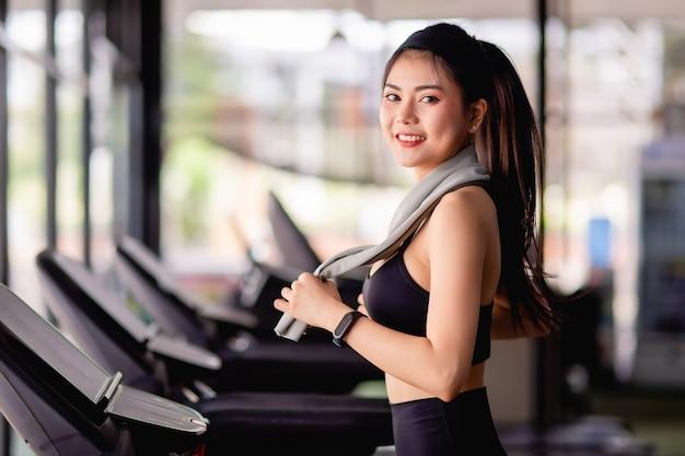 Jonge sexy vrouw die sportkleding draagt, zweetbestendige stof en smartwatch gebruikt handdoek veeg zweet tijdens training in moderne sportschool, glimlach, kopieer ruimte