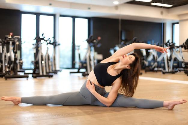 Jonge sexy vrouw die uitrekkende oefeningen in gymnastiek doet