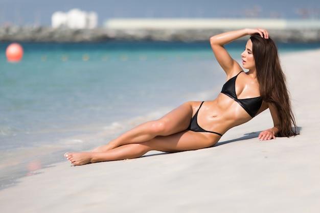 Jonge sexy vrouw die van een zonnige dag op tropisch strand geniet