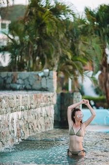 Jonge sexy vrouw die van rust op de rand van openlucht zwembad geniet