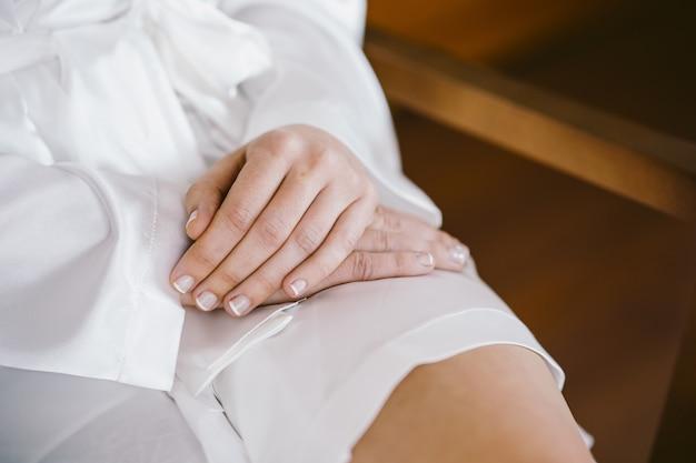 Jonge sexy vrouw die witte kousen draagt die op haar slanke benen leggen.