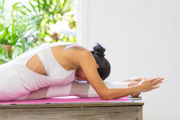 Jonge sexy vrouw die yogaoefening thuis doet.