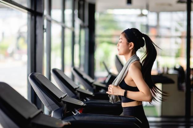 Jonge sexy vrouw draagt sportkleding, zweetbestendige stof en smartwatch die op de loopband loopt om te trainen in de moderne sportschool, glimlach, kopieer ruimte Gratis Foto