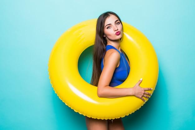 Jonge sexy vrouw in bikini binnen opblaasbare ring geïsoleerd op groene muur