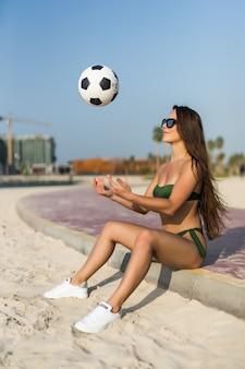 Jonge sexy vrouw in bikinispel met bal op het strand