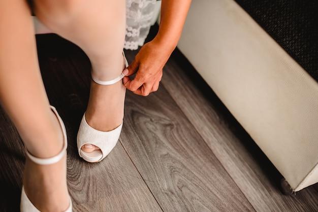 Jonge sexy vrouw in lingerie die de post van haar witte schoenen dichtknopen.