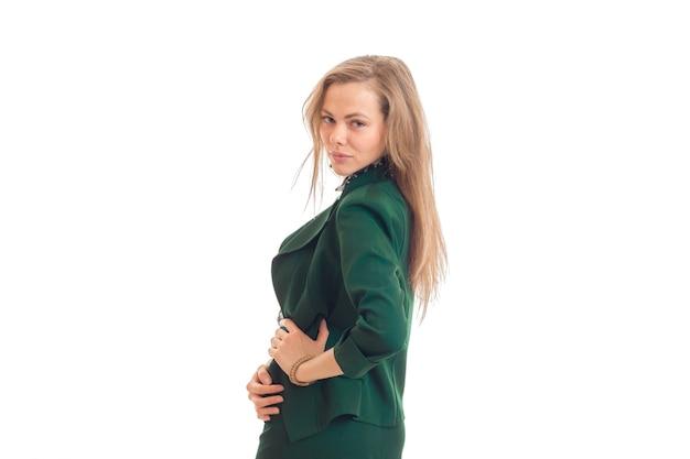 Jonge sexy vrouw in pak staat zijwaarts en kijkt rechtstreeks in de camera geïsoleerd op een witte muur