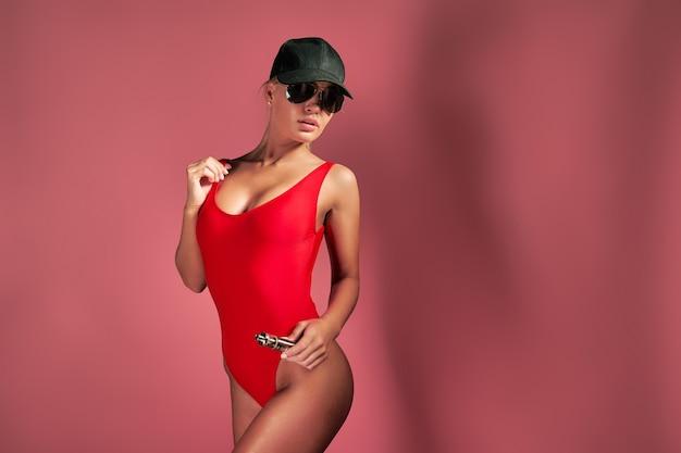 Jonge sexy vrouw in rode zwembroek en pet is vapen poseren op studio roze achtergrond een wolk van damp