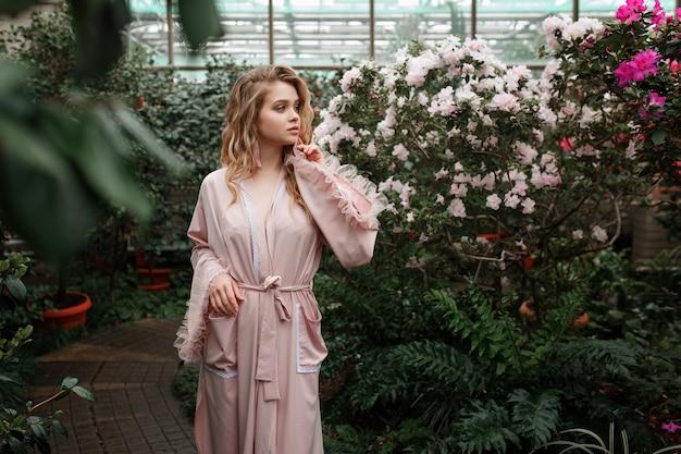 Jonge sexy vrouw in roze badjas staande in de ochtend tuin vol met bloemen