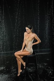 Jonge sexy vrouw in witte lingerie. water studio foto.