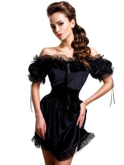 Jonge sexy vrouw in zwarte jurk poseren op witte muur