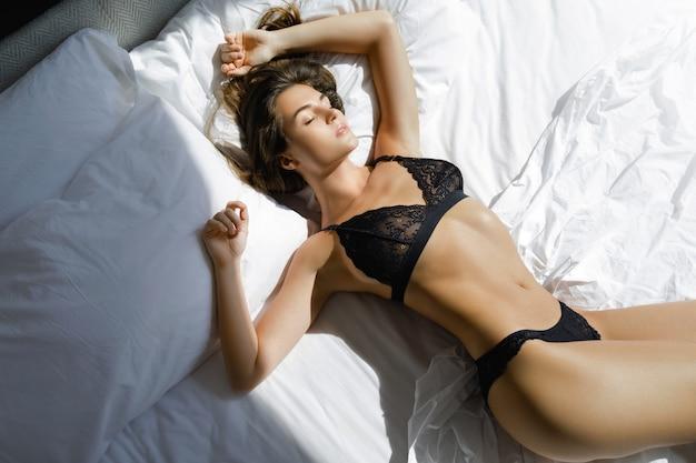 Jonge sexy vrouw in zwarte lingerie liggend op het bed