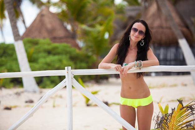 Jonge sexy vrouw in zwempak dichtbij witte omheining bij exotische toevlucht