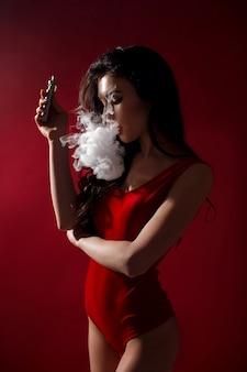 Jonge sexy vrouw is vapen. een wolk van damp.