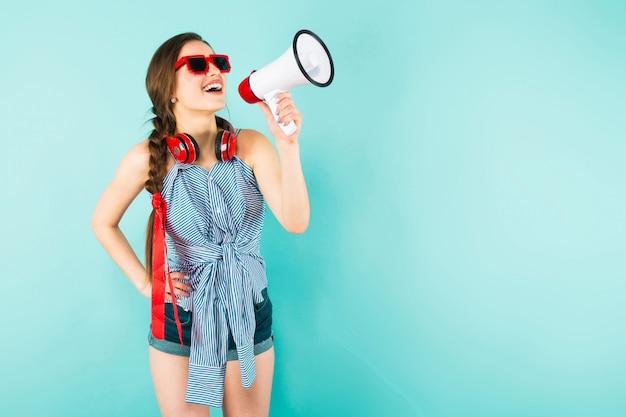 Jonge sexy vrouw met een koptelefoon en luidspreker