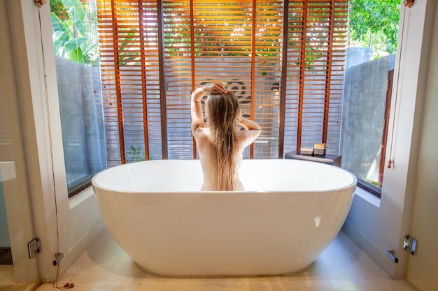 Jonge sexy vrouw nemen van een bad met schuim. gelukkig lachend vrouw ontspannen in badkuip