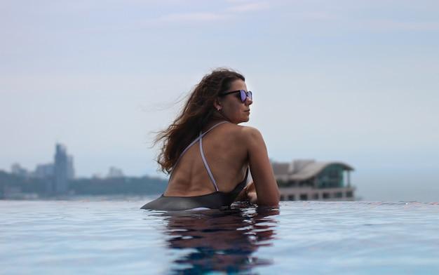 Jonge sexy vrouw ontspannen in het zwembad op het dak en genieten van prachtig uitzicht over de stad.