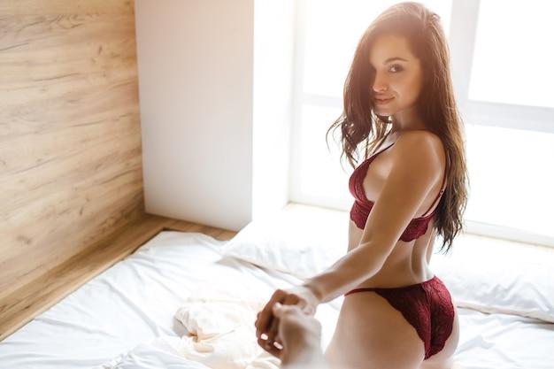 Jonge sexy vrouw op bed. houd de hand van een man vast en kijk terug op de camera. draag mooie hete rode lingerie. sexy bikini. smakelijke vrouwenglimlach met hartstocht.